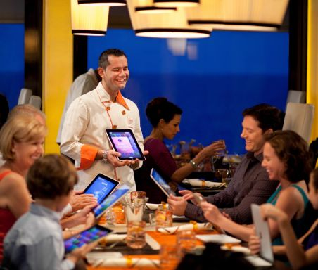 A waiter with an iPad and wearing a white apron smiles at a group in a restaurant