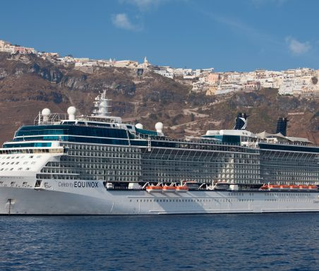 A large white cruise ship sails on the ocean in the sun, a city on top of the mountains is in the background.