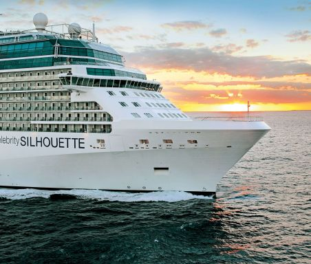 A large white cruise ship sails on the ocean at sunset.