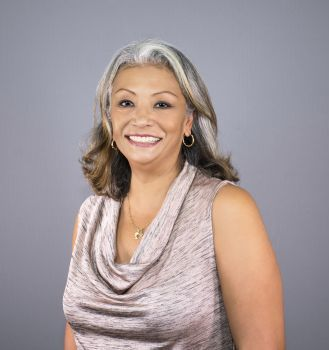 A woman with grey hair and a sparkly shirt smiles at the camera.