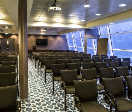 A conference room full of brown chairs with windows along one side.