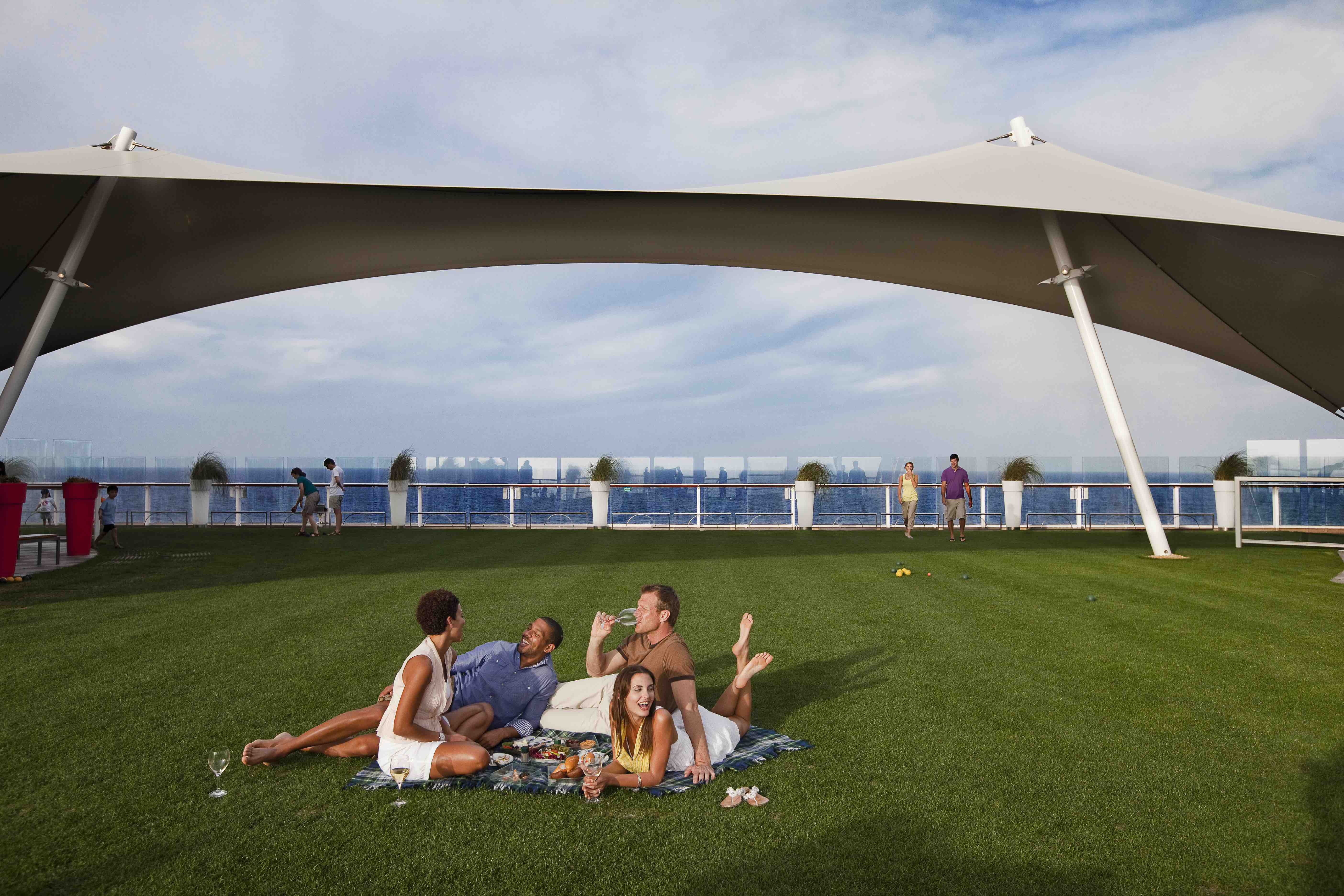 Group of friends having a picnic on the Lawn Club onboard Celebrity Solstice